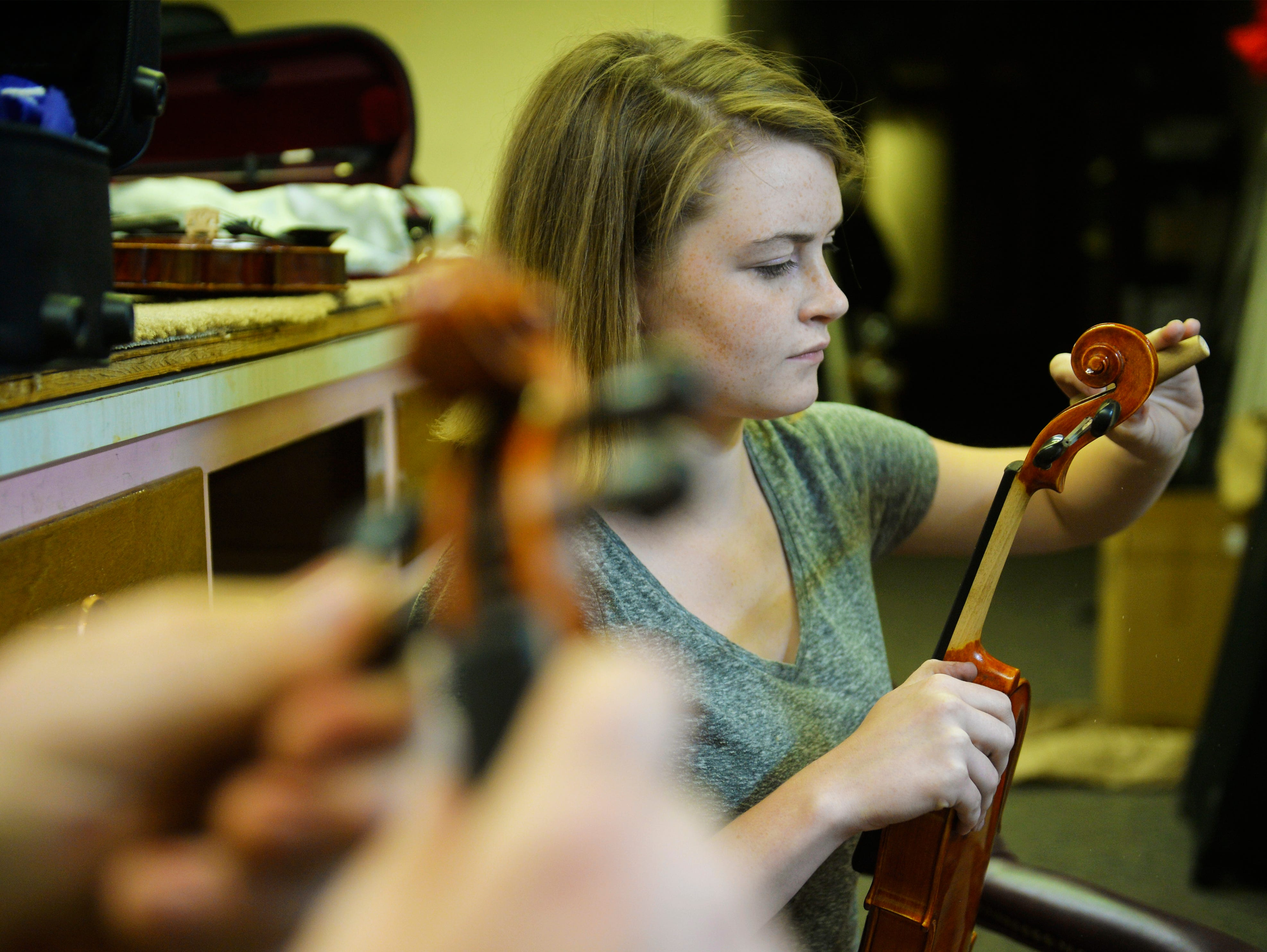 Kailey Dunbar assembles a rental violin at Bass Clef School of Music and Fine Art, recently.