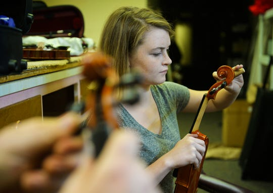 Kailey Dunbar assembles a rental violin at Bass Clef School of Music and Fine Arts.
