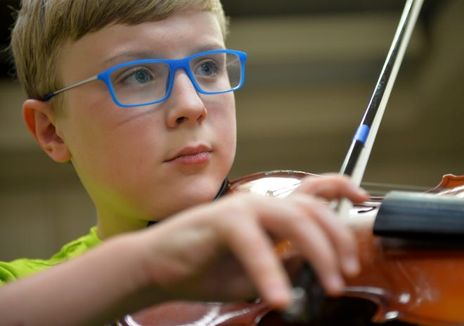 D.J. Loessberg takes a violin lesson from Kailey Dunbar at the Bass Clef School of Music and Fine Arts.