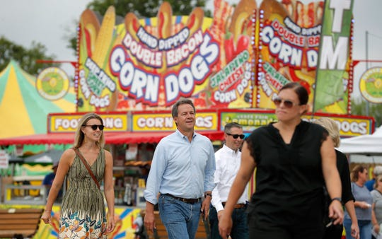 Montana Gov. Steve Bullock, center, walks down the main concourse during a visit to the Iowa State Fair, in August in Des Moines.