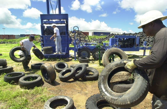 In this 2003 file photo, Gino Ngirasechedui, right, Mike Libingston, center, and Ariel Navarro, feed old tires to a baler at a Ko`Ku Recycling lot in Barrigada Heights. Ko'Ku Recycling has been waiting 17 years for the government to pay for the removal of about 50,000 metric tons of metallic waste, including junk cars nand debris, caused by Typhoon Paka.