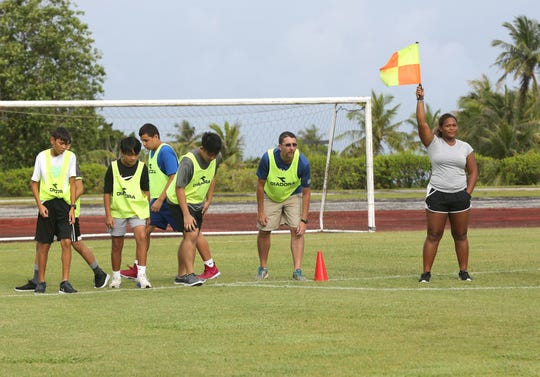 Guam Football Association youth administrator and national assistant referee Franshay Shippey, with flag, signals the start of one segment of the referee fitness test at the 2018 GFA referee camp at LeoPalace Resort Guam.