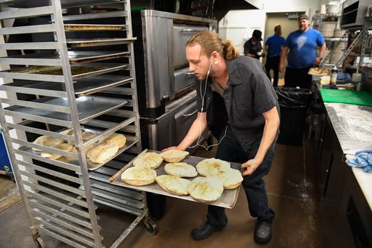 Working in the kitchen at the Farmer & Frenchman Winery, Josh Wersith puts a tray of fresh baked panini bread on a rack to cool for the lunch time crowd, Wednesday, August 15, 2018.