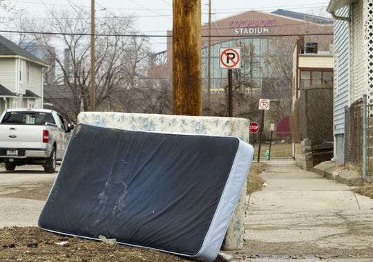 Old mattresses are piled against a utility pole on Kansas Street about 1/2 mile south of Lucas Oil Stadium on Feb. 16, 2011.