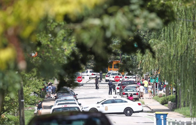 Indianapolis police and concerned parents wait on the perimeter of Tech High School following a reported series of brawls at the school on Thursday, Aug. 16, 2018.