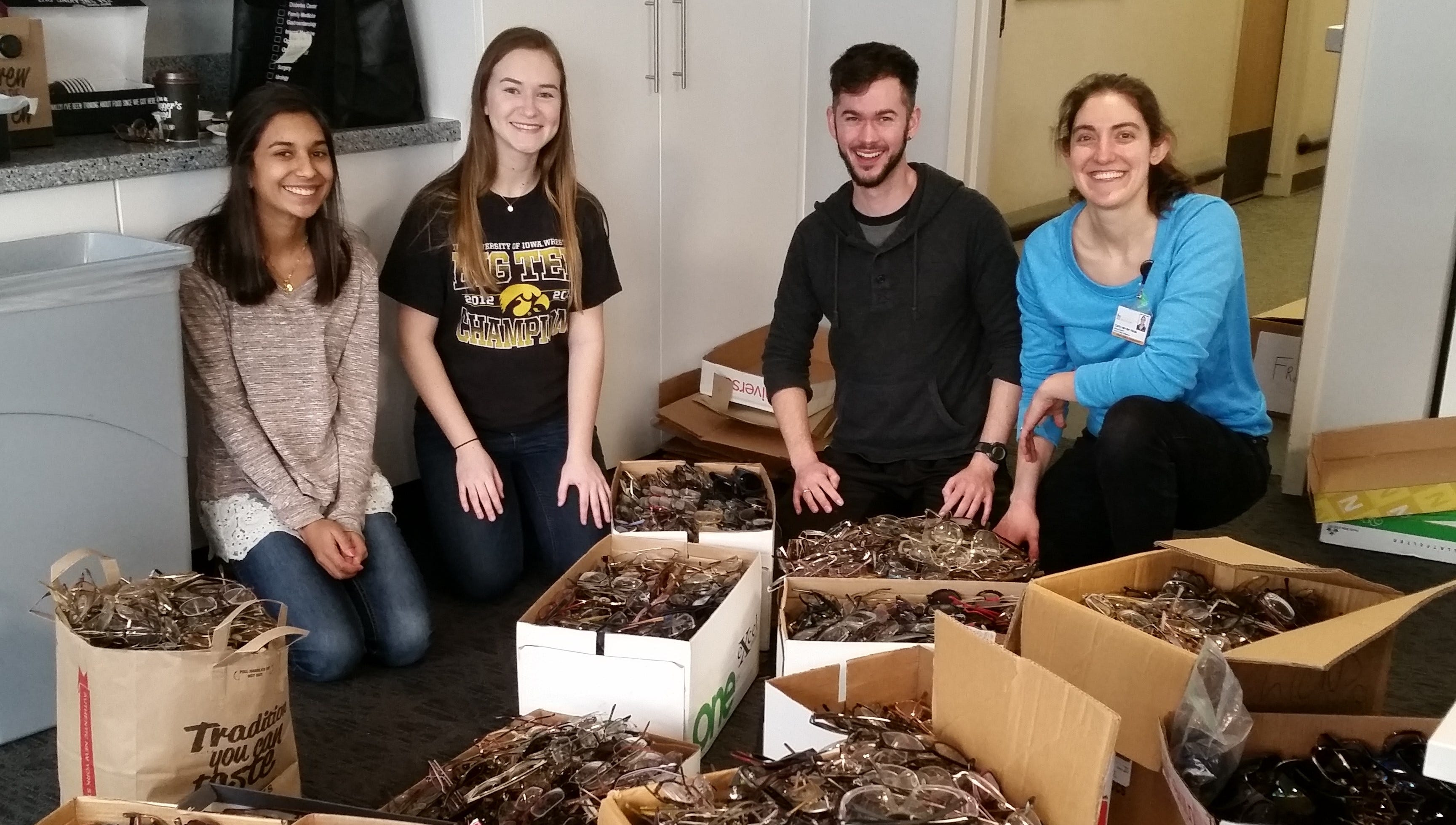 University of Iowa student volunteers (from left) Megan D'Mello, Klaudia Rejczak, Addison Woll and Carly Van Der Heide prepare to process boxes of donated glasses collected from individuals and Lions Club sources.  The glasses are cleaned, then prescriptions are read and logged into the ReSpectacle database, then matched with recipients and  shipped where needed in the U.S. and abroad.