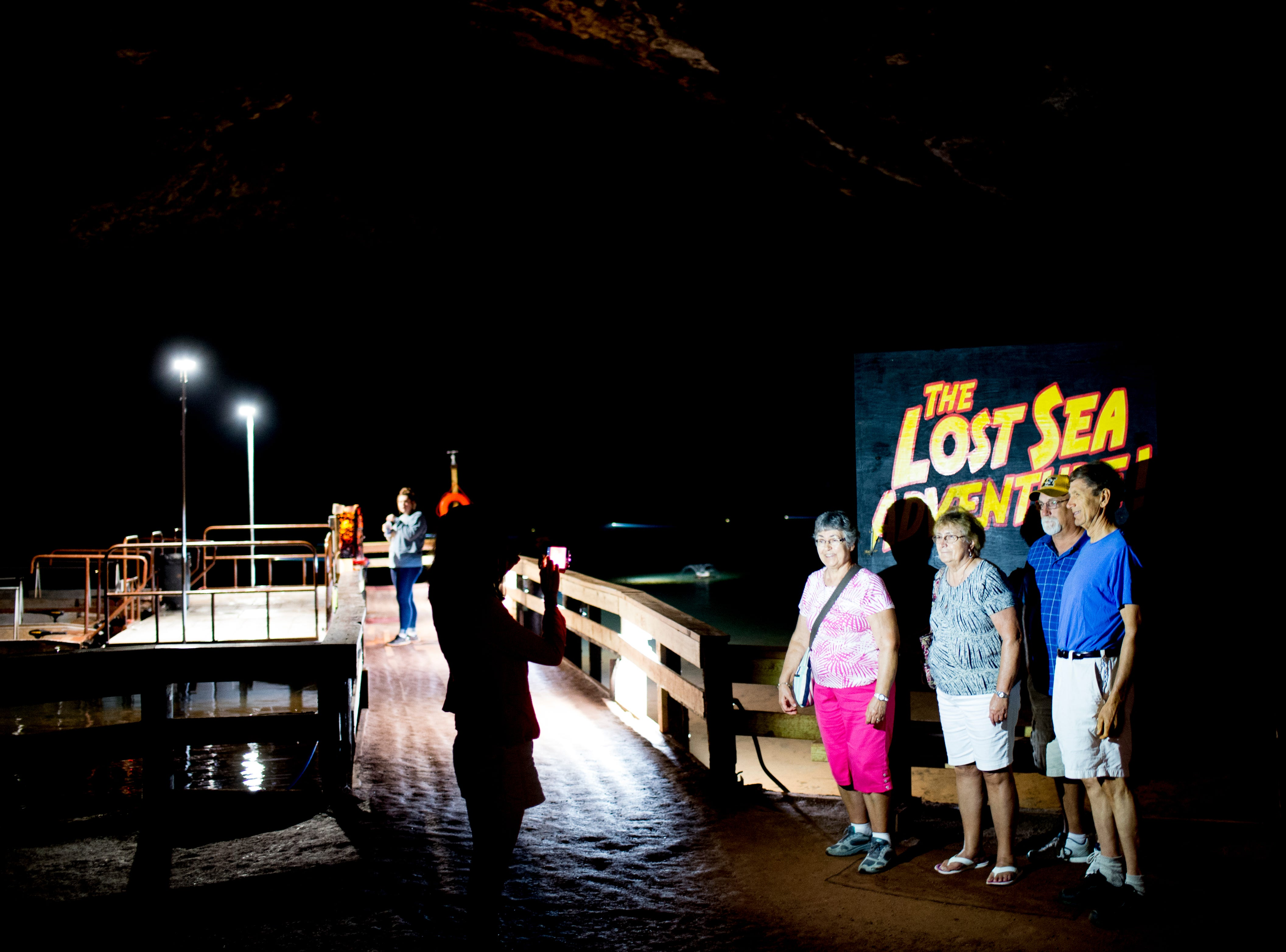 Visitors snap a photo beside the lake at the Lost Sea Adventure underground cave attraction outside of Sweetwater, Tennessee on Wednesday, August 15, 2018. The cave system dates back some 20,000 years and today features points of interests like an old moonshine still, rock formations, Confederate Army graffiti and the popular boat ride in a natural lake stocked with 200 rainbow trout.