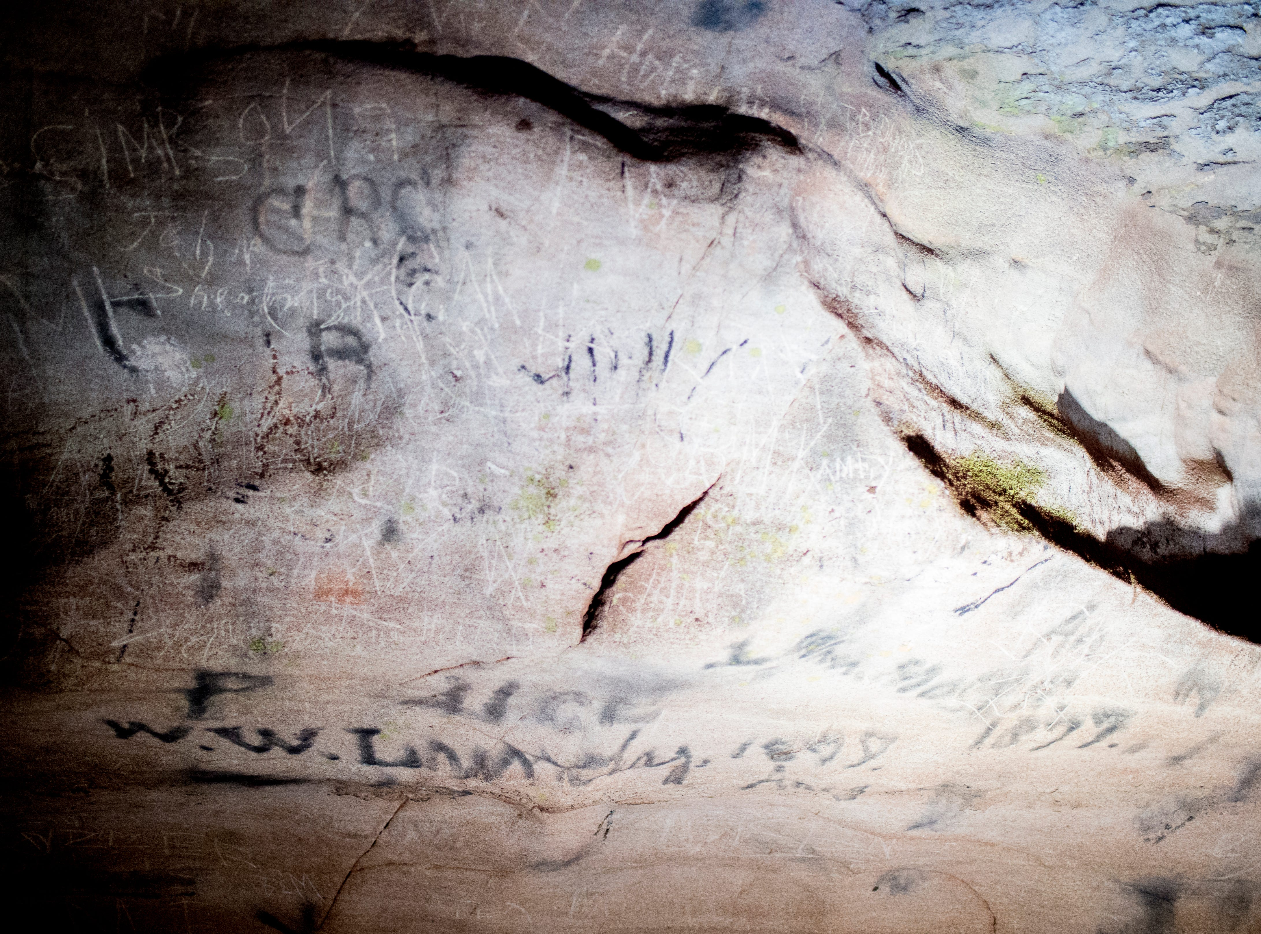 Graffiti, including Confederate Army graffiti seen in black, is etched into the cave walls at the Lost Sea Adventure underground cave attraction outside of Sweetwater, Tennessee on Wednesday, August 15, 2018. The cave system dates back some 20,000 years and today features points of interests like an old moonshine still, rock formations, Confederate Army graffiti and the popular boat ride in a natural lake stocked with 200 rainbow trout.