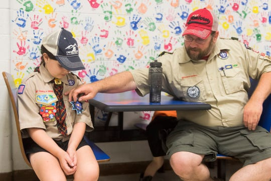 Randy Ross straightens a Cub Scout badge on his daughter Cassidy's uniform at the Pack 506 recruitment drive at Halls Elementary School on Wednesday, August 15, 2018.