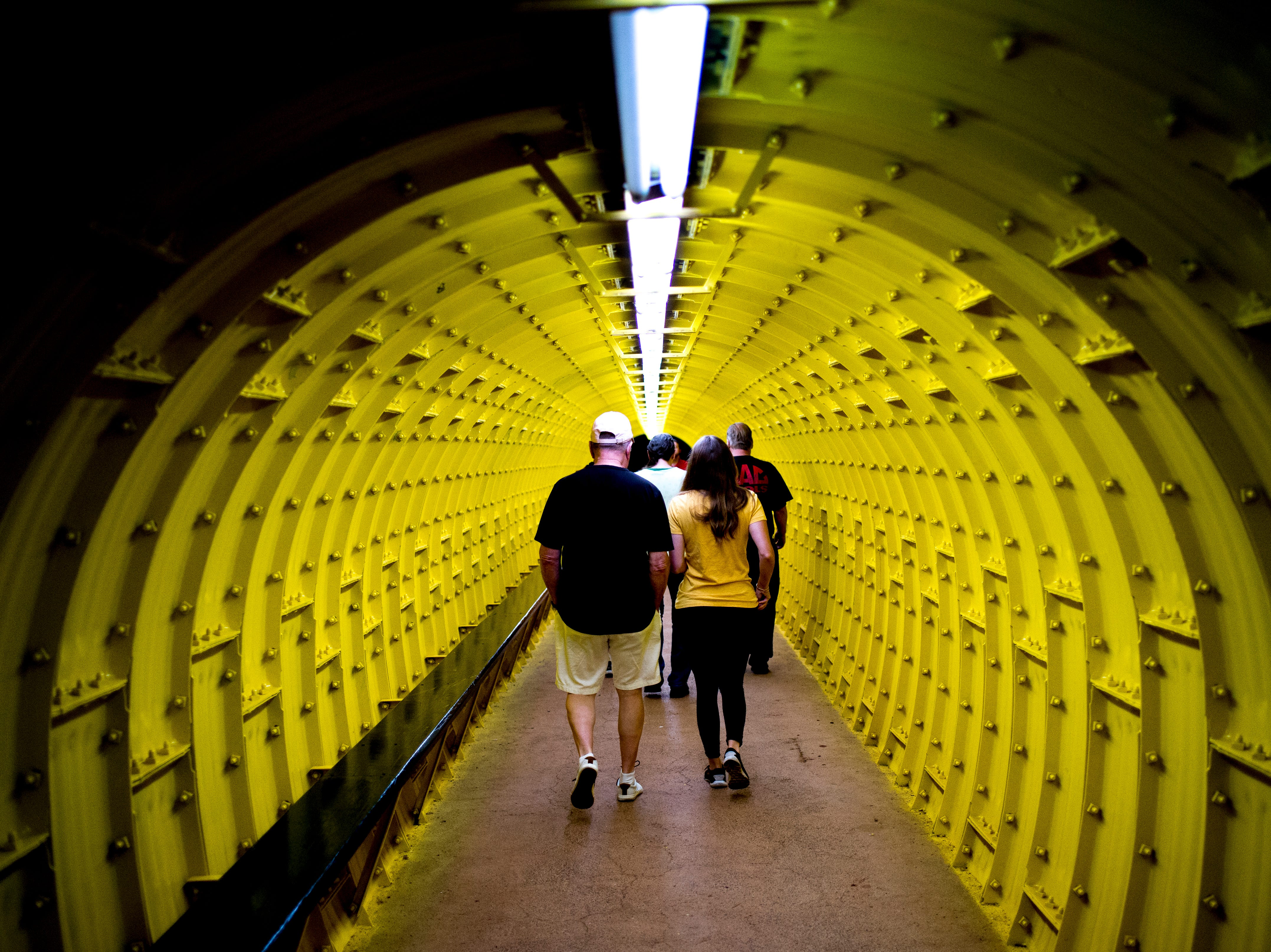 Visitors walk down a tunnel to reach the caves at the Lost Sea Adventure underground cave attraction outside of Sweetwater, Tennessee on Wednesday, August 15, 2018. The cave system dates back some 20,000 years and today features points of interests like an old moonshine still, rock formations, Confederate Army graffiti and the popular boat ride in a natural lake stocked with 200 rainbow trout.