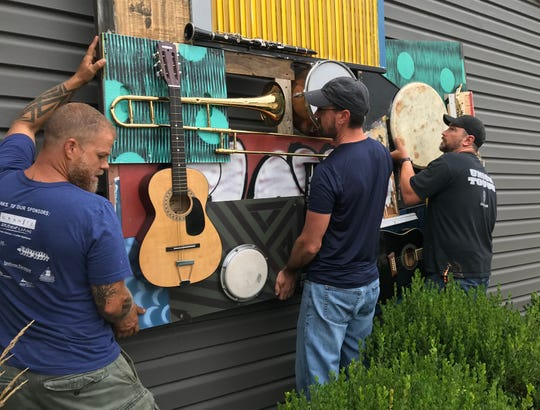 "Josh Bible, left, Zach Medler and Trent O'Brien position ""Play Music Everywhere,"" Medler's piece in the Wabash Walls art project, on Sacred Grounds, a coffee shop at 724 Wabash Ave. on Thursday, Aug. 16."