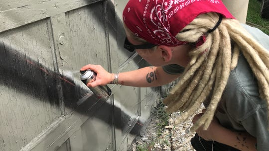 Jenna Morello, an artist from Brooklyn, works Thursday, Aug. 16, on a mural on the wall of the former Seyfert's Potato Chips building on Wabash Avenue. She was part of the Wabash Walls art project.