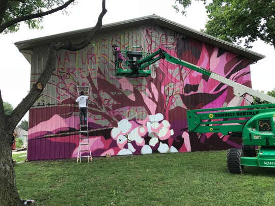 """Nicole """"Nico"""" Holderbaum, on the lift, and Trevor Stevens work on a mural on the side of a Habitat for Humanity Barn on Williams Street on Thursday, Aug. 16. The work is part of Wabash Wall, an art project in Lafayette's Wabash Avenue Neighborhood."""