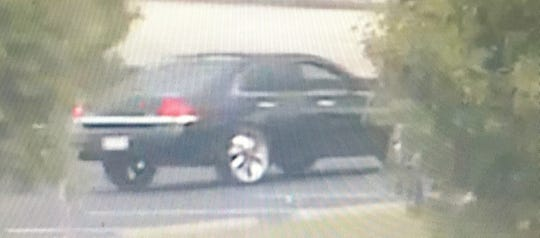 This black  car with tinted windows -- possibly a Chevy Impala -- was driven by two women suspected to have stolen wallets from women's purses on Friday.