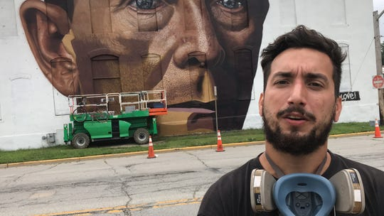 Andres Cobre discusses his mural of a train conductor on a Lafayette Sanitation Department barn on Second Street, part of the Wabash Walls art project, on Thursday, Aug. 16, 2018.