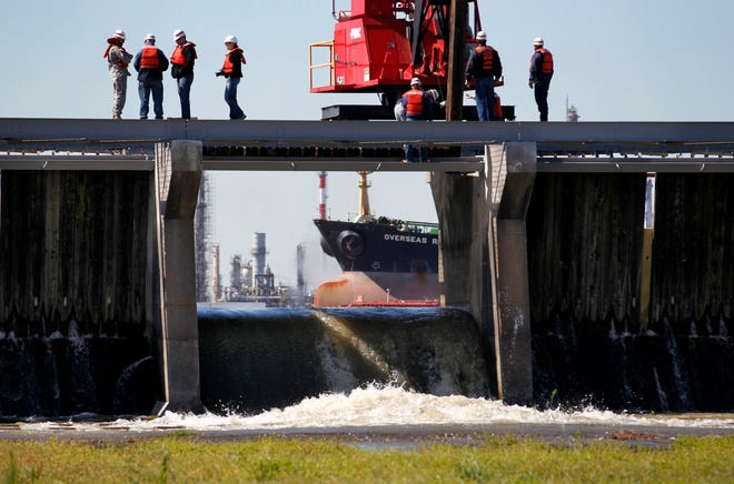 FILE - In this April 5, 2011, file photo, a tanker ship and refinery on the Mississippi River are seen while water rushes into the Bonnet Carre Spillway, that leads from the river to Lake Pontchartrain, as employees of the U.S. Army Corps of Engineers practice removing one of the 350 bays of the river control structure, in Norco, La. The FBI is keenly aware of the dangers that cyber-criminals pose to Mississippi River-related businesses and south Louisiana infrastructure. And the agency wants the public at large to be aware, as well. (AP Photo/Gerald Herbert, File)