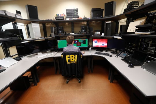 In this Tuesday, July 31, 2018, photo, an FBI employee works in a computer forensics lab at the FBI field office in New Orleans. More than 20 people working for the FBI headquarters in Louisiana are working on cyber security. They include experts working at forensics labs, doing forensics on computer hard drives and developing techniques for analyzing computer memories in efforts to fight and find intruders, according to the special agent in charge of the FBI's New Orleans field office.