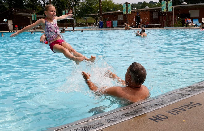 Zoe Wayner, 8, from Athens, launches into the air from her hands of her grandfater Gary Green, from Lancaster, Wednesday, Aug. 15, 2018, in Lancaster. Attendance was up at all of the Lancaster Parks and Recreation pools this summer.