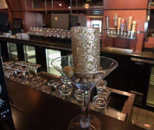 A candle reflecting the martini theme sits on a bar empty of activity Thursday, Aug. 16, 2018 at the Downtown Main Martini Bar & Grille, except for the boxing of items by owners Nick and Lindsay Palizzi, not visible in the background.