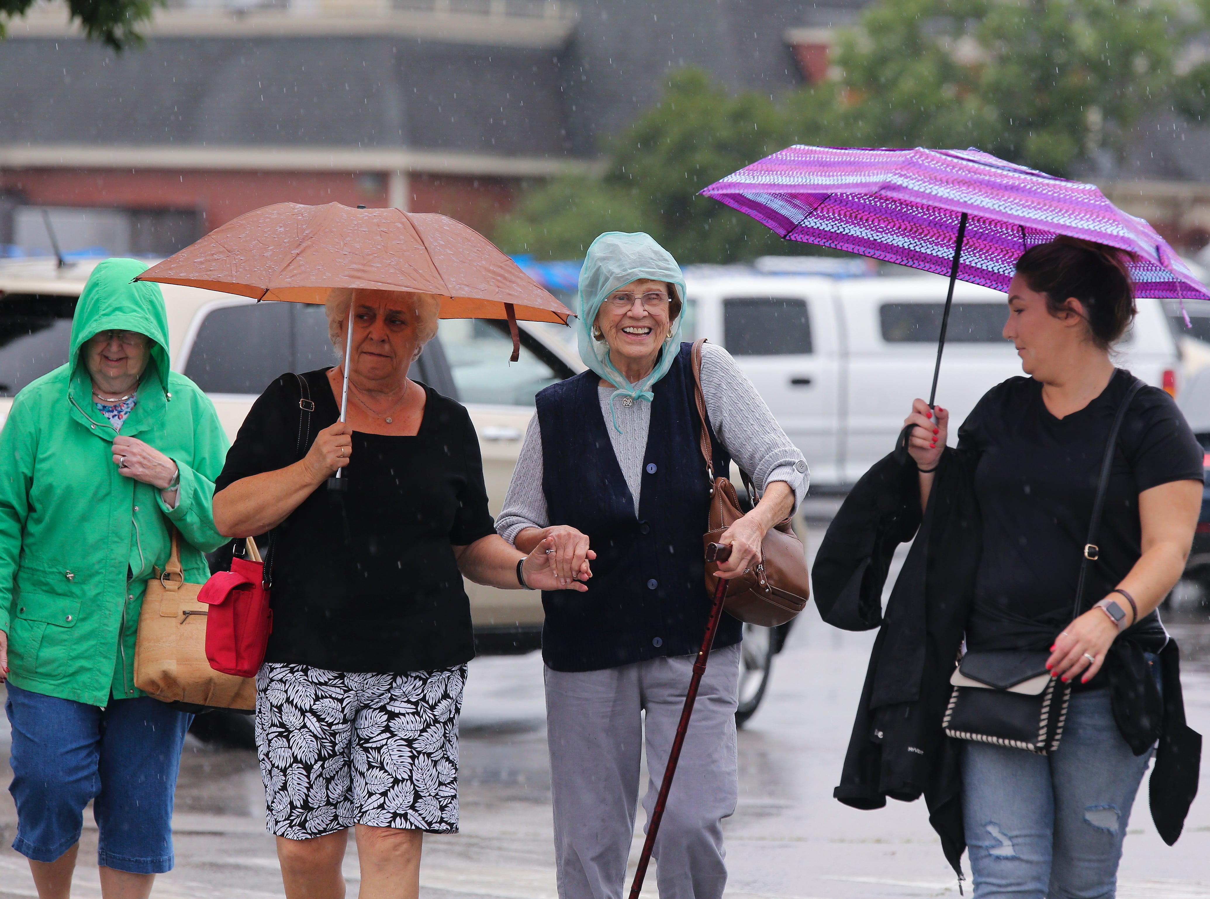 Stella Lindaur, center, who is 99-years-old, got some assistance walking in the rain from her niece Arlene Rigsby, left, on the first day of the Kentucky State Fair.  Lindaur's great-great niece Danielle Stivers was at right.Aug. 16, 2018