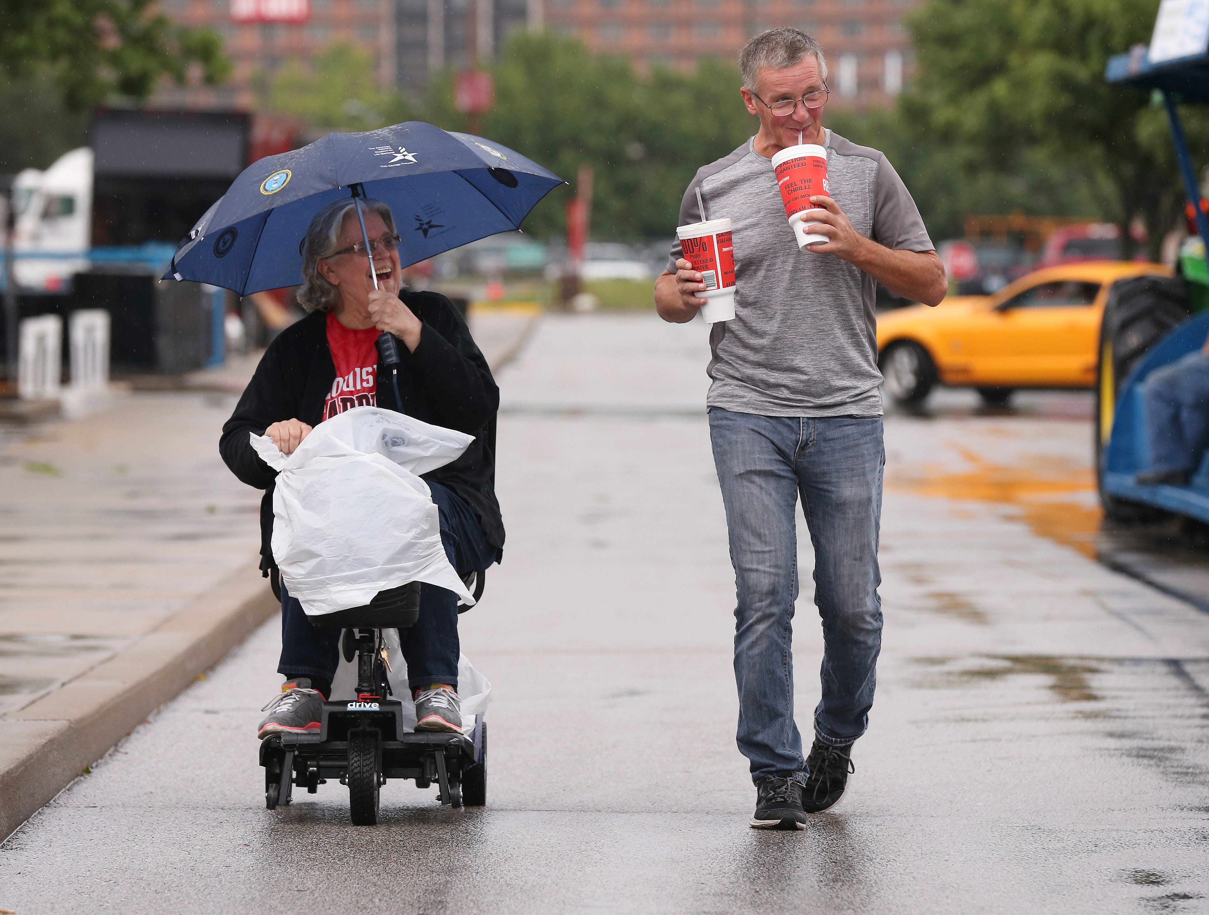 Pat Reynolds, left, used a motorized scooter as she and her son Kevin Anderson arrived in the rain on the first day of the Kentucky State Fair.Aug. 16, 2018