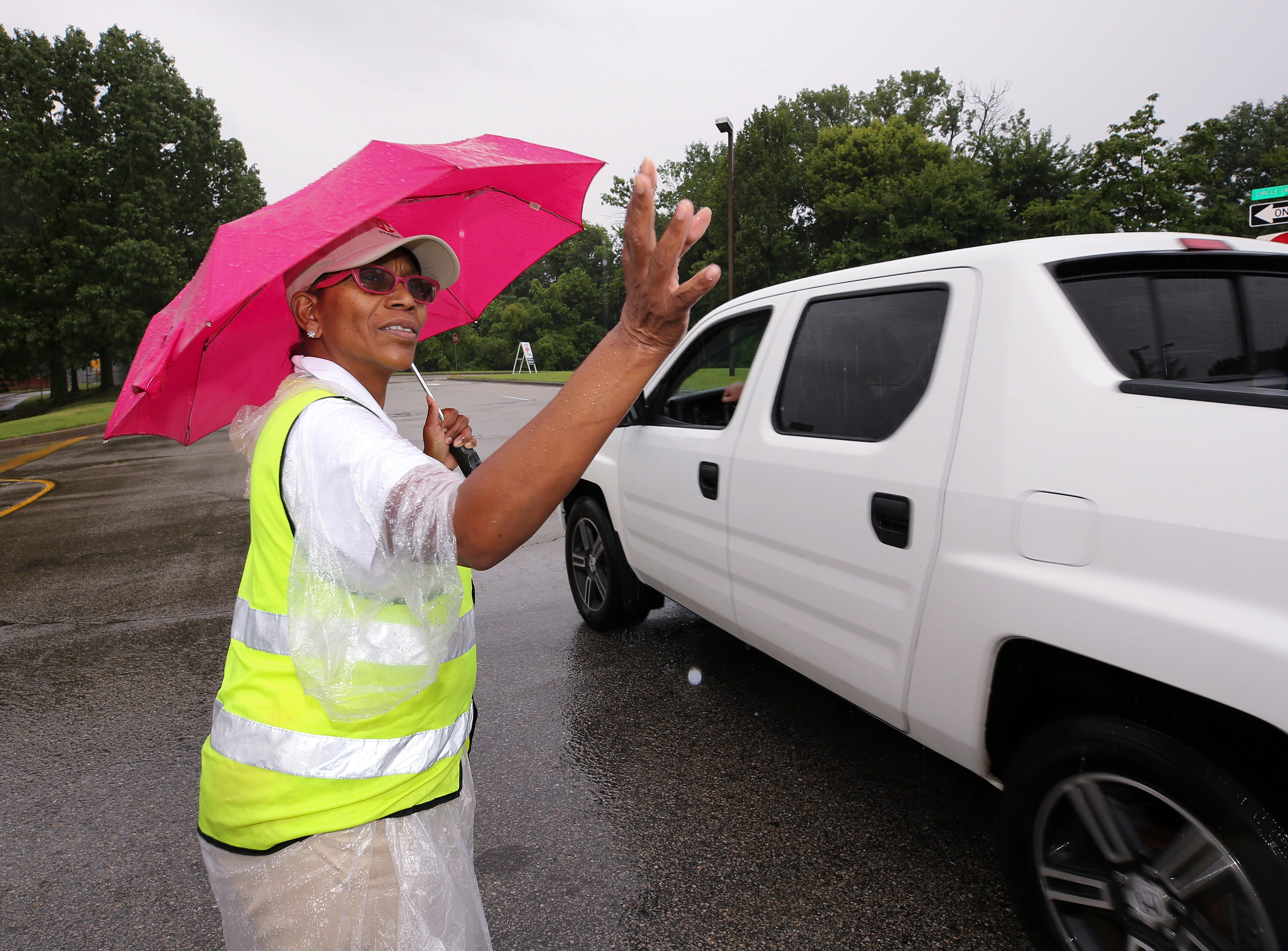 Tracy Harris directs traffic in the rain on the first day of the Kentucky State Fair.Aug. 16, 2018
