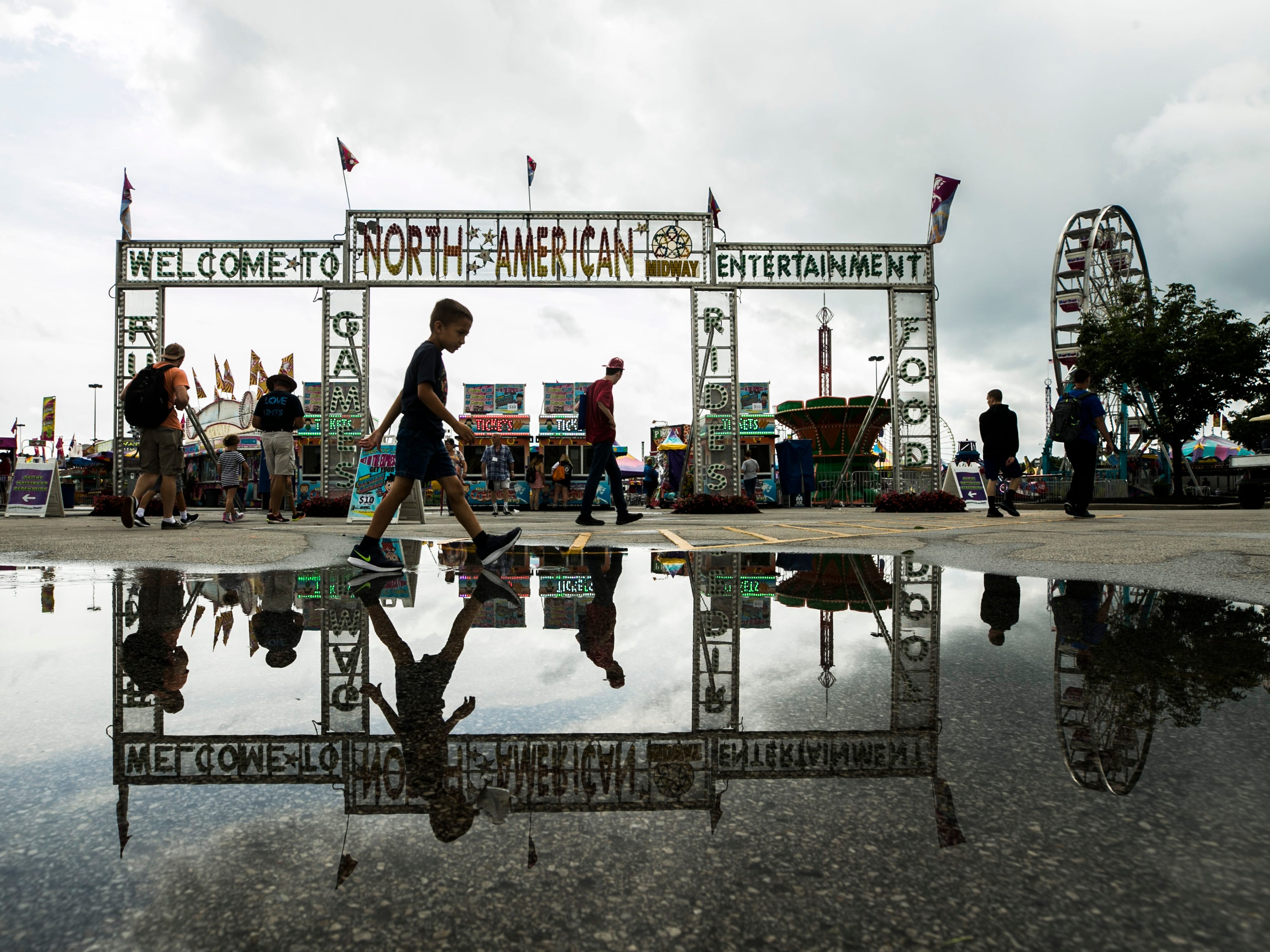 It was a rainy morning on the opening day of the 2018 Kentucky State Fair but by early afternoon, the rain stopped and the sun peaked out on the midway, with puddles helping cast a mirror image.