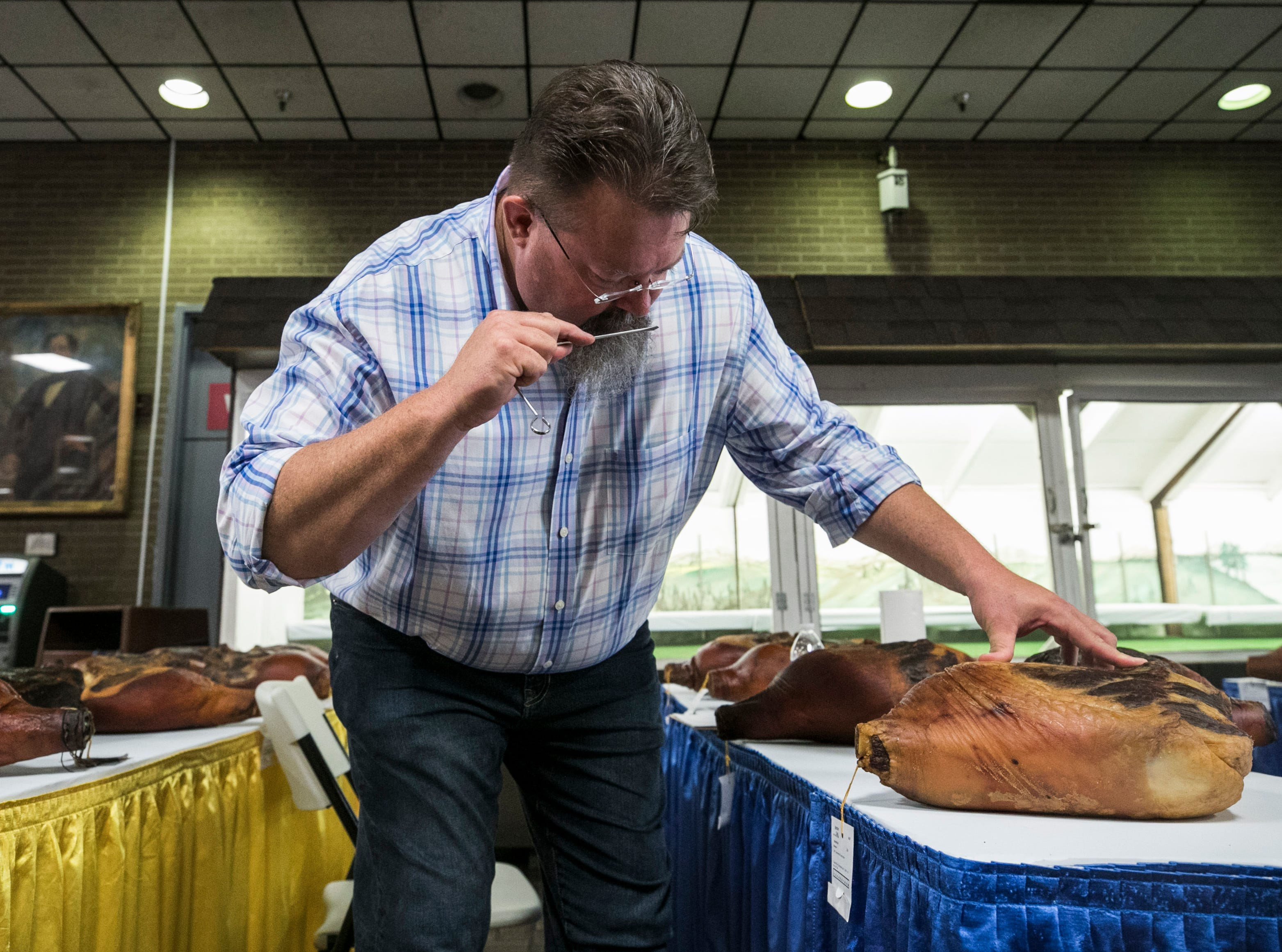 Associate professor Dana Hanson of North Carolina State University judges the country hams on the first day of the Kentucky State Fair. Hanson was looking for a 'meaty' smell when he probes the ham in two places, making sure it doesn't smell sour or rancid. He's also looking for a tan color, but not too light or 'charcoal' from smoking. The top ham will be auctioned off at the Country Ham Breakfast later.