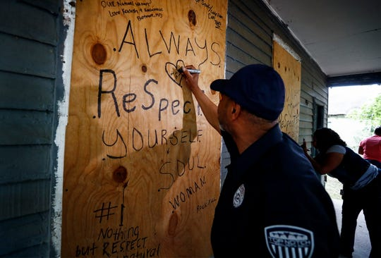 Minister Michael D. Richards writes a message on the house where Aretha Franklin was born in South Memphis on Thursday morning. Franklin died earlier in the morning in Detroit.