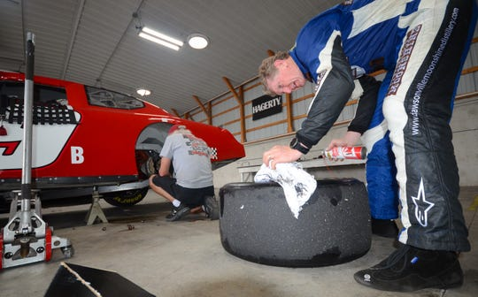 Bill Elliott cleans grease off a tire after an axle came out of his vintage Dodge stock car Thursday.