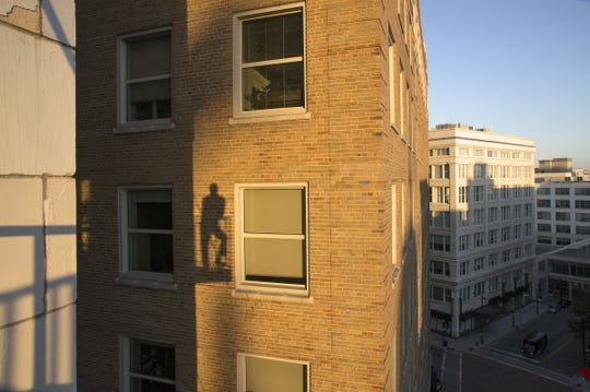 Dick Blau's shadow is visible on the building next door as he takes photographs from his downtown balcony.