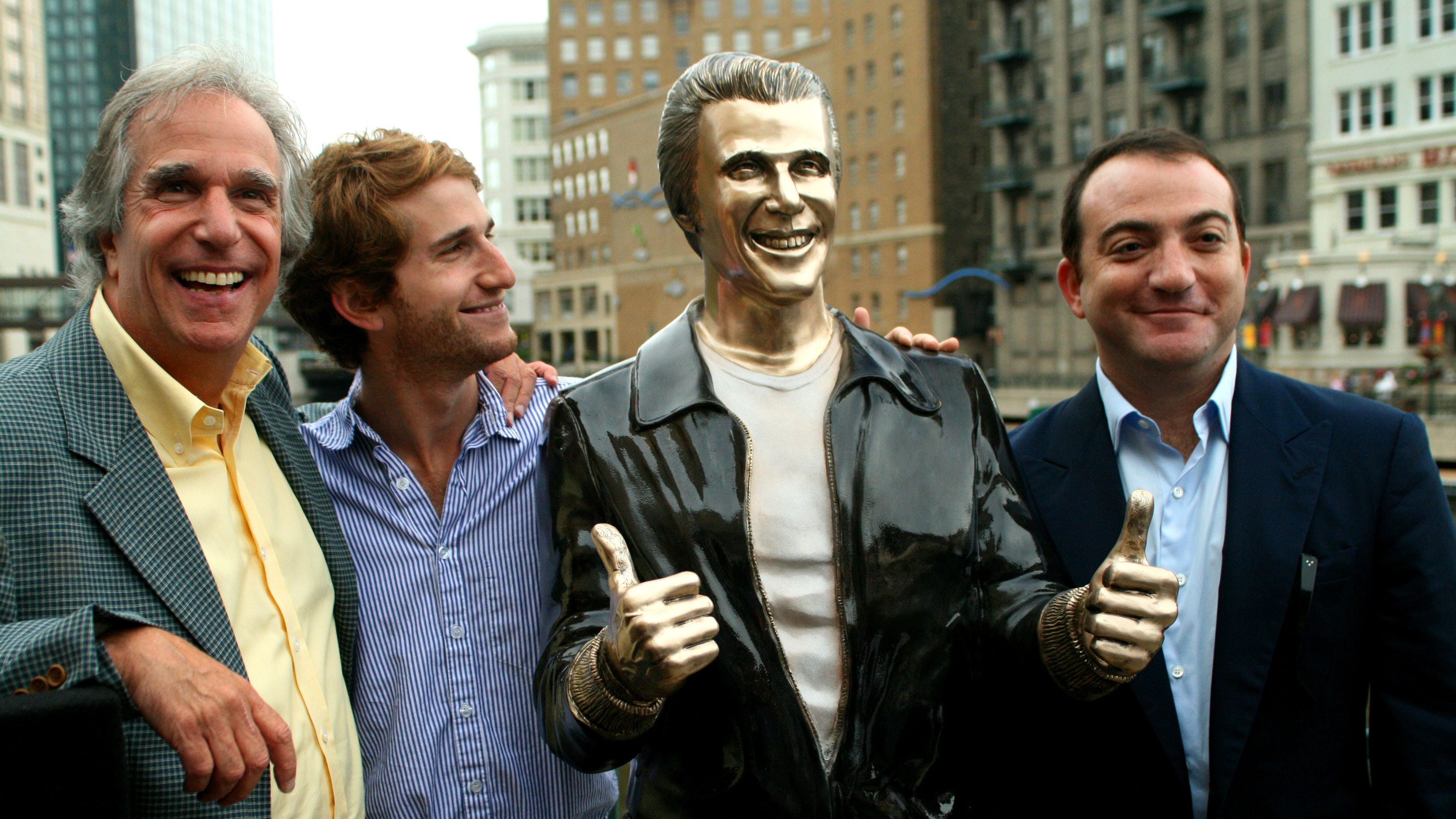 "Actor Henry Winkler, left, poses with his sons Max Winkler, second left, and Jed Weitzman as they stand with a bronze statue of the ""Happy Days"" character Arthur Fonzarelli, also known as ""The Fonz,"" at an unveiling, Aug. 19, 2008, in Milwaukee. The program, which ran from 1974-1984, was based in Milwaukee."