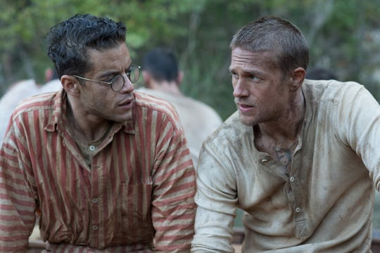 "Rami Malek (left) and Charlie Hunnam play unlikely comrades plotting an escape from the prison on Devil's Island in ""Papillon."""