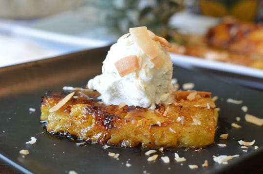 Grilled pineapple topped with ice cream makes a sweet summer dessert.