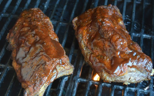 After ribs are done, they're returned to the grill with a coating of barbecue sauce.