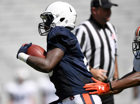 Auburn running back Asa Martin outruns a defender during a scrimmage on Wednesday, Aug. 15, 2018 in Auburn, Ala.