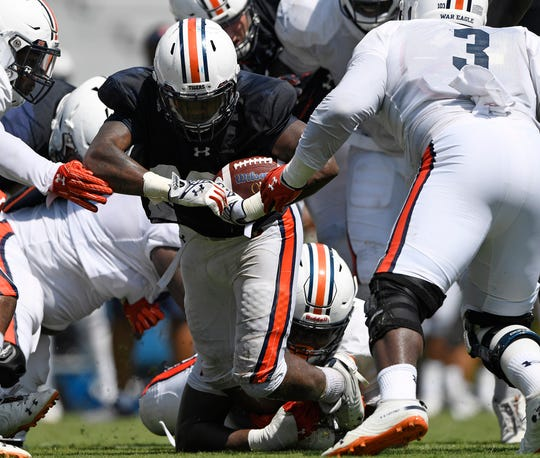 Auburn running back JaTarvious Whitlow is tackled by Derrick Brown during a scrimmage on Wednesday, Aug. 15, 2018 in Auburn, Ala.