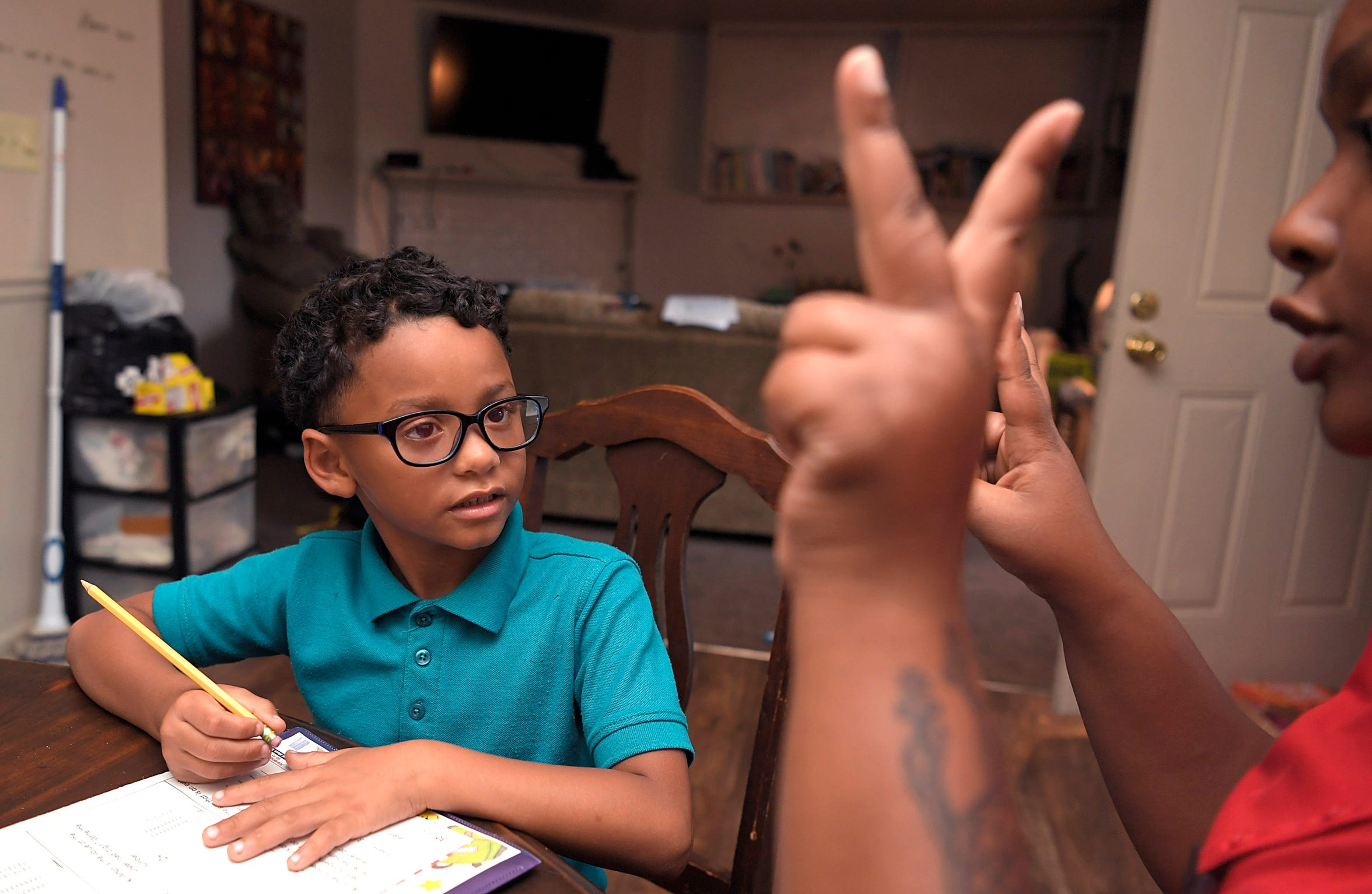 Shaunqueen Leatherman helps her son Johnathan do his homework at their North Nashville home Aug. 16, 2018.