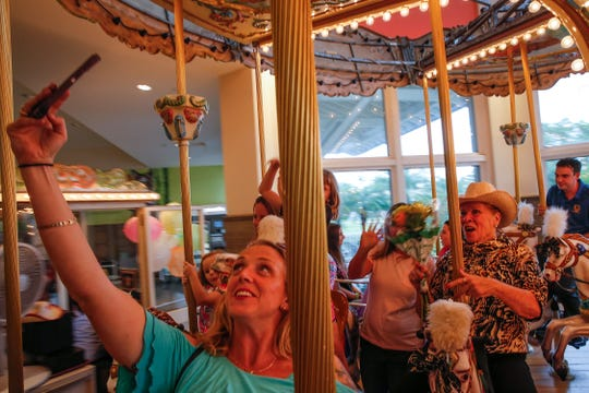 Greta Marszalkowski, one of the parents who helped prepare a surprise gift for Coastland Center carousel operator  Mary Warder, right, takes a selfie as they ride the carousel Tuesday, Aug. 14, 2018. Parents from the Naples Moms 2.0 Facebook group raised money to buy Warder a reliable car. Known as Miss Mary, she has worked at  the Coastland Center carousel for many years.