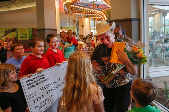 Mary Warder embraces each of the children Tuesday, Aug. 14, 2018, who came for her surprise presentation of $5,000 to replace her broken-down car. Known as Miss Mary, she has worked at the Coastland Center mall carousel for many years.