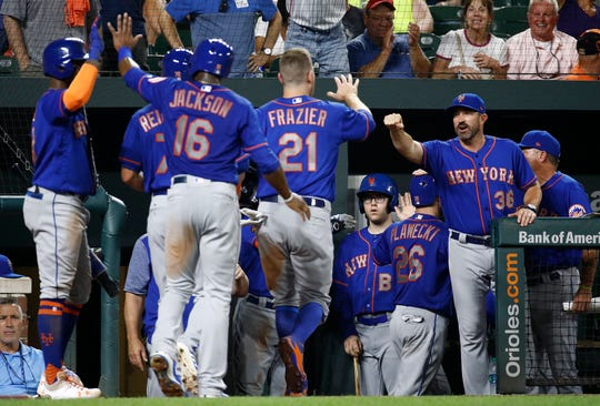 New York Mets manager Mickey Callaway, right, greets Todd Frazier (21) after Frazier scored on Kevin Plawecki's grand slam during the sixth inning of a baseball game against the Baltimore Orioles, Wednesday, Aug. 15, 2018, in Baltimore.