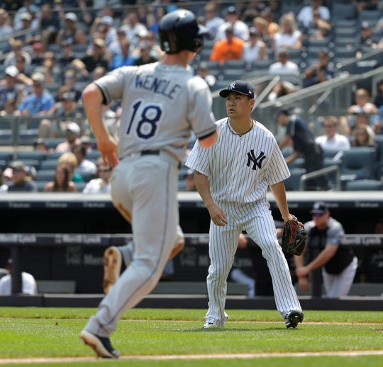 New York Yankees starting pitcher Masahiro Tanaka, right, looks after the ball as Tampa Bay Rays' Joey Wendle runs home to score during the first inning of a baseball game at Yankee Stadium Thursday, Aug. 16, 2018, in New York.