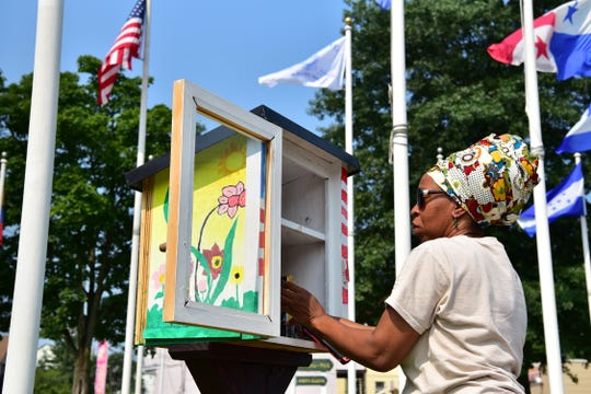 Talena Lachalle Queen stocks books at the Little Free Library drop box at Pan American Park in Paterson, NJ.