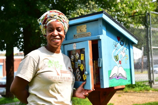 Talena Lachalle Queen poses for a photo at The Little Free Library drop box in Paterson, NJ.