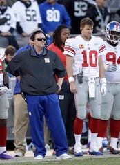 New York Giants head coach Ben McAdoo, left, stands next to quarterback Eli Manning (10) during the second half against the Oakland Raiders in Oakland, Calif., Sunday, Dec. 3, 2017. Manning's consecutive starting streak ended at 210 games. McAdoo was fired the next day.