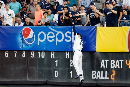 New York Yankees right fielder Neil Walker (14) makes an out on a fly ball by Tampa Bay Rays catcher Michael Perez (43) during the second inning at Yankee Stadium.