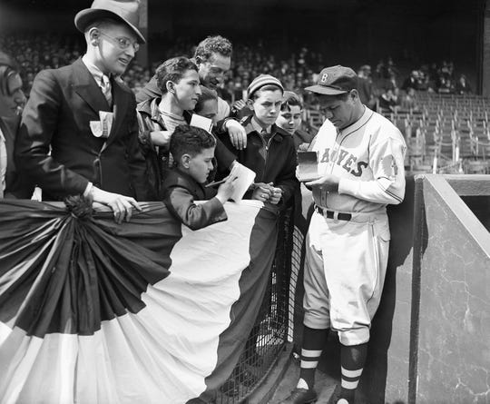 Playing with the Boston Braves, Babe Ruth signs autographs for fans at the New York Giants' home opener against the Braves at the Polo Grounds. New York, April 23, 1935.