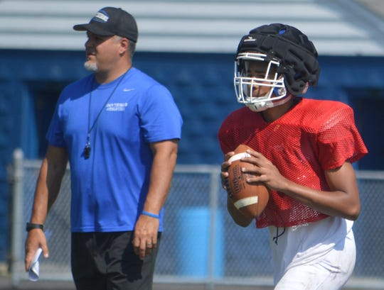 Hawthorne football coach John Passero watching as senior quarterback T.J. Palmer throws a pass against Saddle Brook in a scrimmage last week.