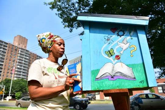 Talena Lachalle Queen stocks books at the Little Free Library drop box at Tyrone Collins Park in Paterson, NJ.