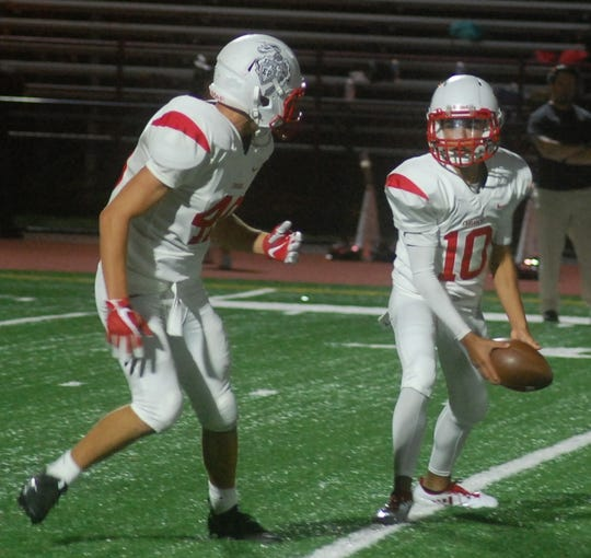 Elmwood Park quarterback Joey Leto pitches out to running back Eddie Alfieri in a 2018 game.